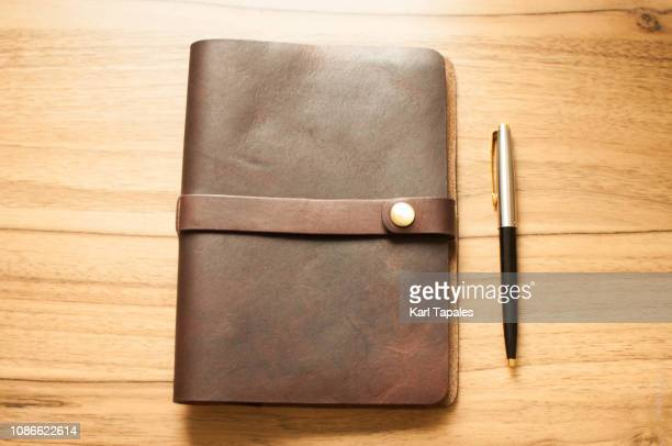 a leather-bound personal organizer on a wooden table - viewpoint stock pictures, royalty-free photos & images