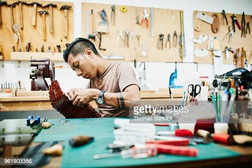 Leatherworker hand making purse in workshop