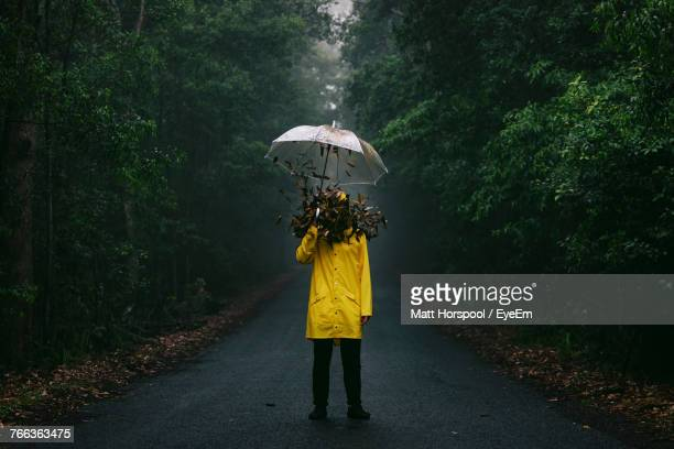 Leaves Falling On Man Holding Umbrella