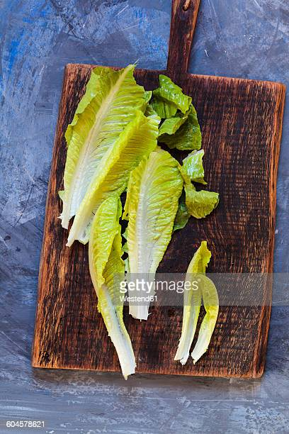leaves of romaine lettuce on wooden board - romaine lettuce stock photos and pictures