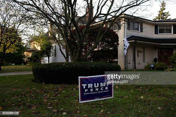 Leaves surround a campaign sign for Republican presidential nominee Donald Trump displayed on the same block where Democratic presidential nominee...