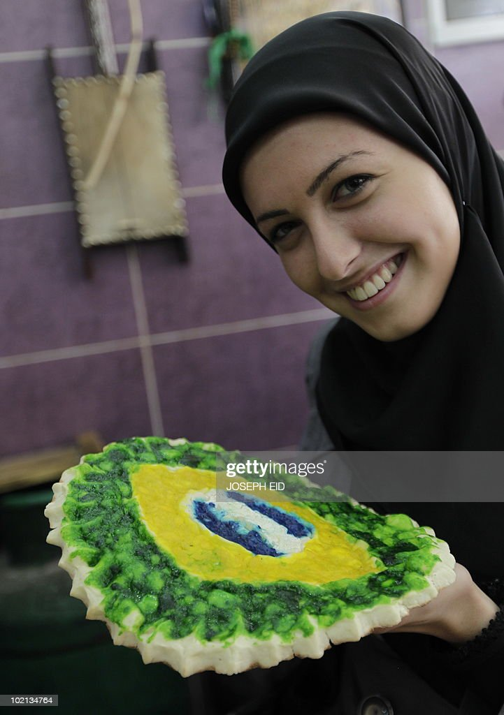 A Lebanes woman holds a 'special-edition World Cup 2010' traditional Lebanese oven-baked flat bread, covered with cheese and decorated with the Brazilian flag, at a bakery in a southern suburb of Beirut on June 16, 2010.