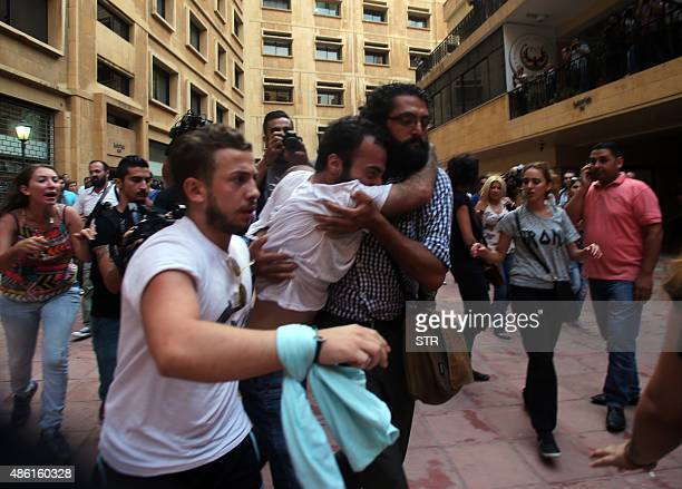 Lebanese activist Lucien Abou Rjeily is carried by fellow demonstrators after activists claim he was beaten by Lebanese police as they started...