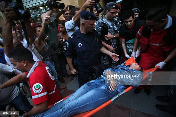 Lebanese activist Neemat Badr Eddine is carried unconscious on a stretcher by first aid medics as she is evacuated from the the environment ministry...
