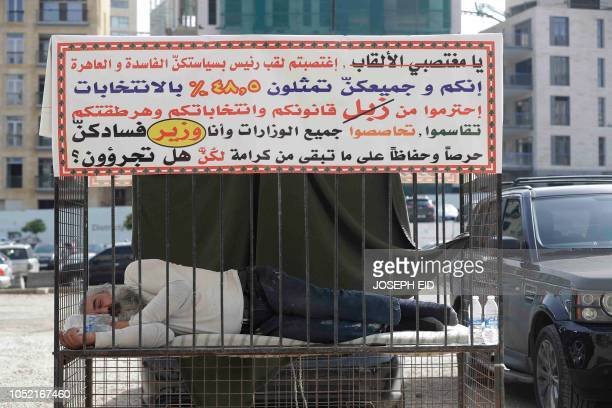 Lebanese activist sleeps inside a cage in Beirut's Martyr's square to protest against the policies of the political elite in Lebanon on October 15...