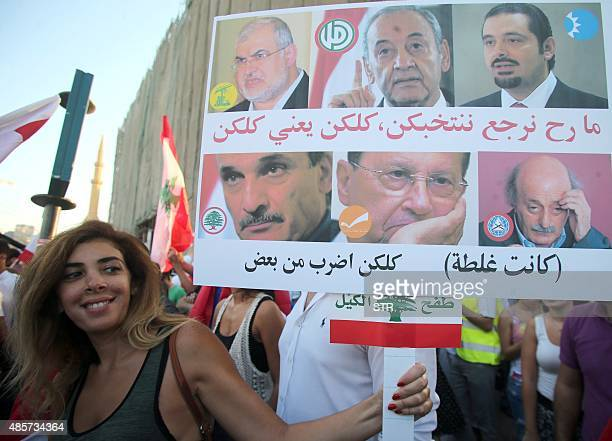 A Lebanese activists holds a placard with portraits of politicians during a mass rally against a political class seen as corrupt and incapable of...