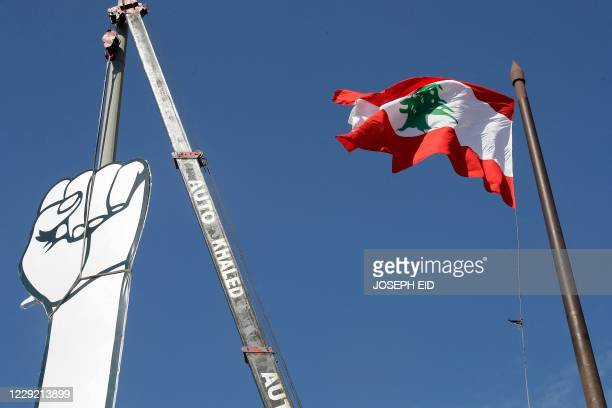 Lebanese activists replace the Revolution fist', symbol of Lebanons October 2019 uprising with a cover made of canvas, a day after the original...