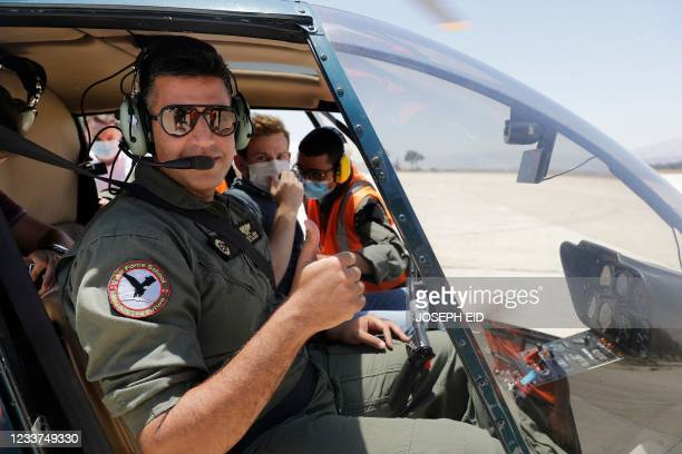 Lebanese Air Force airman gestures while sitting in the cockpit of a Robinson R44 Raven II helicopter giving a press tour at Rayaq military air base...