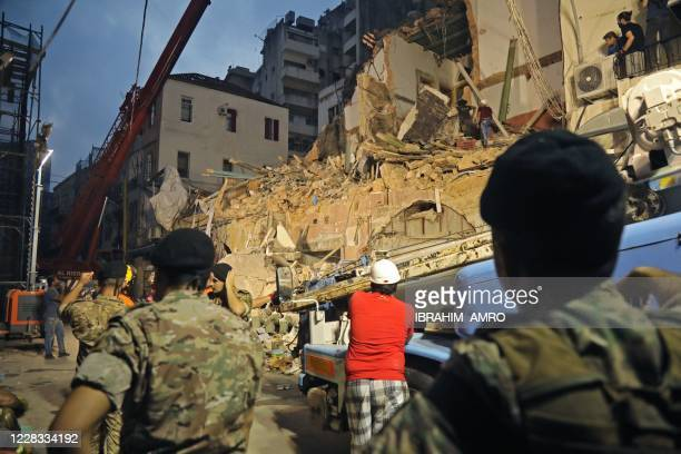 Lebanese and Chilean rescue workers dig through the rubble of a badly damaged building in Lebanon's capital Beirut in search of possible survivors...
