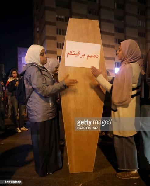 Lebanese anticorruption protesters bang on a fake coffin to denounce the latest suicide cases apparently crushed by the burden of Lebanon's...