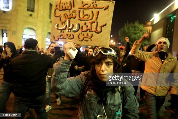 Lebanese anti-corruption protesters shout slogans outside the parliament to denounce the nomination of Prime Minister-designate Hassan Diab in the...