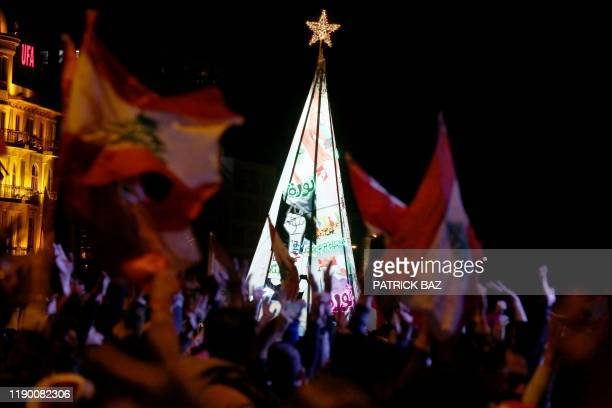 Lebanese anticorruption protesters wave the national flag in front of a Christmas tree erected in Martyr's Square in downtown Beirut on December 22...