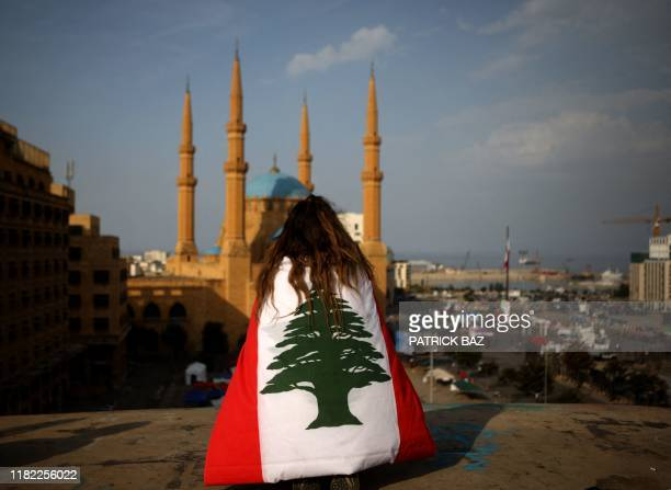 Lebanese anti-government protester, draped in a national flag, sits on the rooftop of 'The Egg' buidling overlooking the Mohammed al-Amin mosque and...