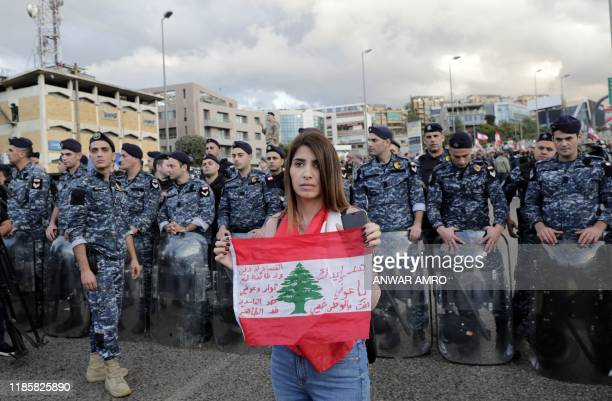 A Lebanese antigovernment protester holds a national flag in front of members of the internal security forces as she takes part in a rally pressing...