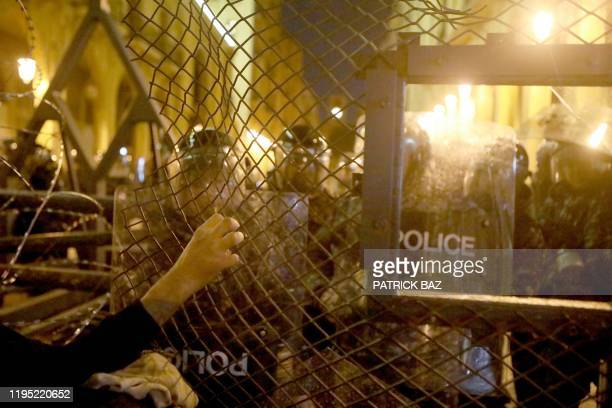 Lebanese anti-government protester holds on to a police fence as riot police guard an access to the parliament during clashes with anti-government...