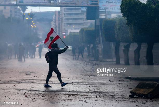 Lebanese anti-government protester waves a national flag during clashes with security forces in front of the Serail , in the northern port city of...