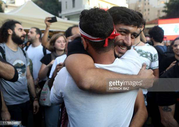 Lebanese antigovernment protesters celebrate the resignation of Prime Minister Saad Hariri in Beirut on October 29 2019 on the 13th day of...