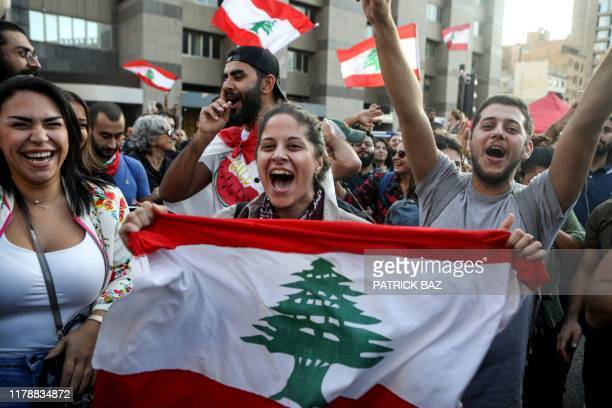 TOPSHOT Lebanese antigovernment protesters celebrate the resignation of Prime Minister Saad Hariri in Beirut on October 29 2019 on the 13th day of...