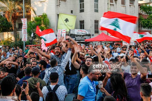Lebanese antigovernment protesters celebrate the resignation of Prime Minister Saad Hariri in the southern city of Sidon on October 29 2019 on the...
