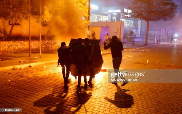 Lebanese antigovernment protesters clash with riot police in the capital Beirut on January 14 2020 Lebanese demonstrators took to the streets to...