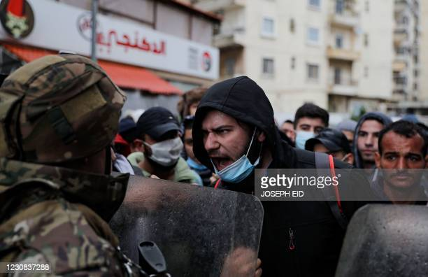 Lebanese anti-government protesters confront security forces as they go around the homes of deputies and government officials in the northern port...
