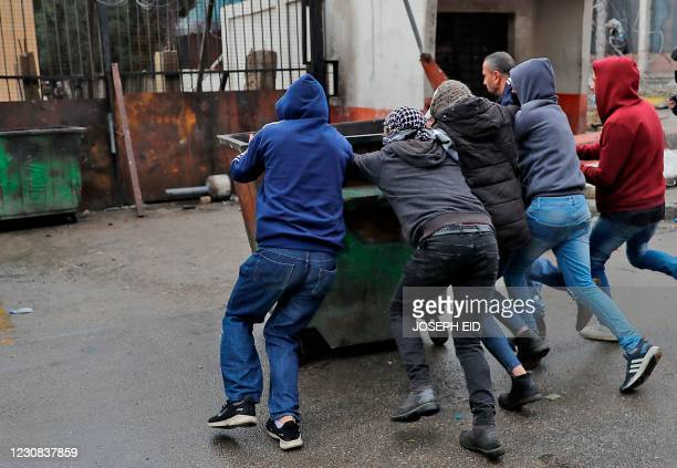 Lebanese anti-government protesters push a garbage container near the Serail , as they clash with security forces in the northern port city of...