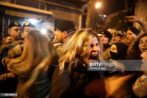 Lebanese antigovernment protesters scuffle with riot police on the eastern end of the Ring bridge that connects the western and eastern...