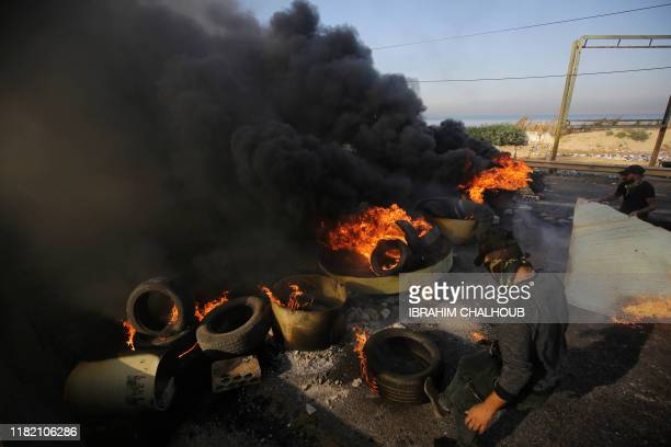 Lebanese antigovernment protesters set tyres on fire to block a main road at the entrance of Tripoli the capital of north Lebanon as antigovernment...