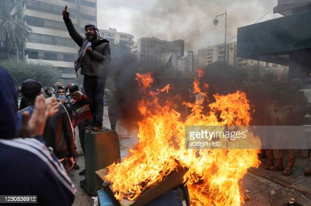 Lebanese anti-government protesters shout slogans and burn a garbage container as they go around the homes of deputies and government officials in...