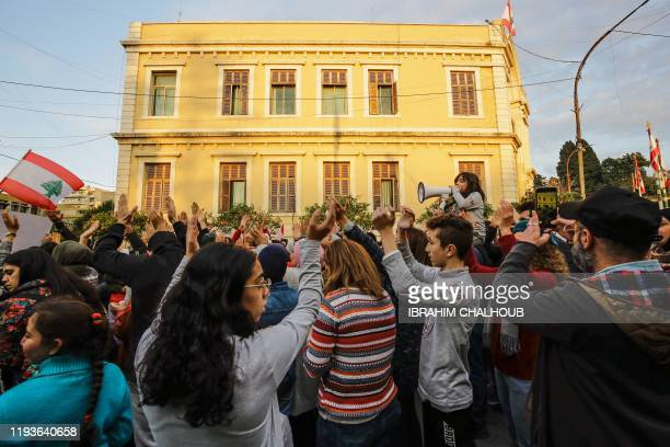 Lebanese antigovernment protesters shout slogans as they march in the streets of the northern port city of Tripoli on January 14 2020 Lebanese...