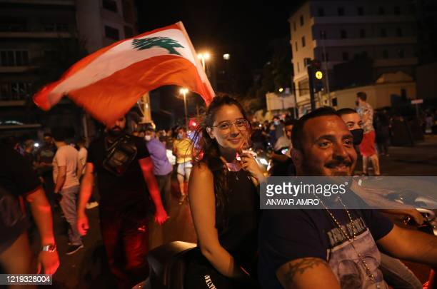 Lebanese anti-government protesters smile as they take part in a demonstration against dire economic conditions, in the downtown district of the...