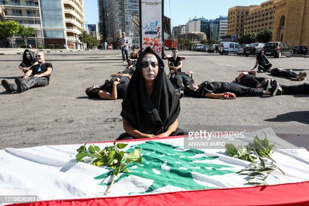 Lebanese anti-government protesters take part in a symbolic funeral for the country in the downtown area of the capital Beirut, on June 13 on the...