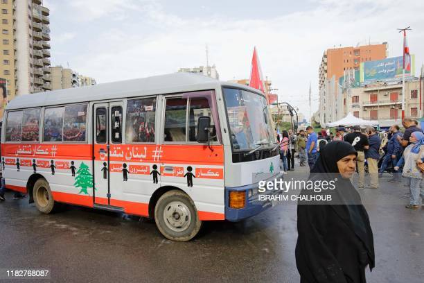 Lebanese antigovernment protesters wait to board a 'revolution' bus heading to south of Lebanon from the northern port city of Tripoli on November 16...
