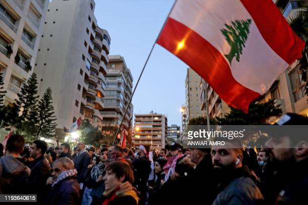 Lebanese anti-government protesters wave a national flag during a rally outside the residence of Lebanon's prime minister designate Hassan Diab in...