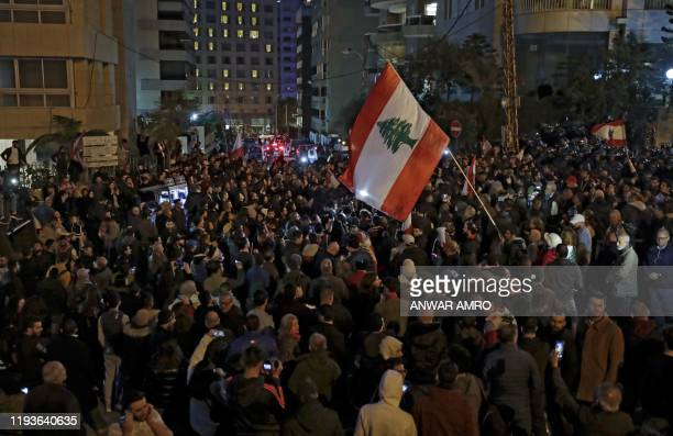 Lebanese anti-government protesters wave national flags during a rally outside the residence of Lebanon's prime minister designate Hassan Diab in the...