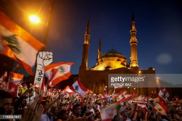 TOPSHOT Lebanese antigovernment protesters wave the national flag during a demonstration in downtown Beirut on November 17 2019 Thousands of Lebanese...