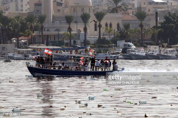 Lebanese antigovernment protesters wave the national flags as they demonstrate on a boat amid floating waste in the waters of the northern port city...