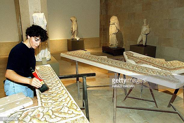 Lebanese archeologist cleans a piece of mosaic at the Lebanese museum 06 October 1999 in Beirut. The museum will be officially reopened 08 October...