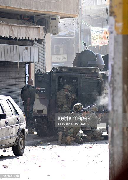 Lebanese armed forces fire as they take cover behind an armoured personal carrier during an assault on Islamist gunmen's makeshift positions inside a...
