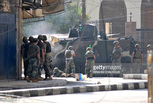 Lebanese armed forces take cover behind an armoured personal carrier during an assault on Islamist gunmen's makeshift positions inside a historic...