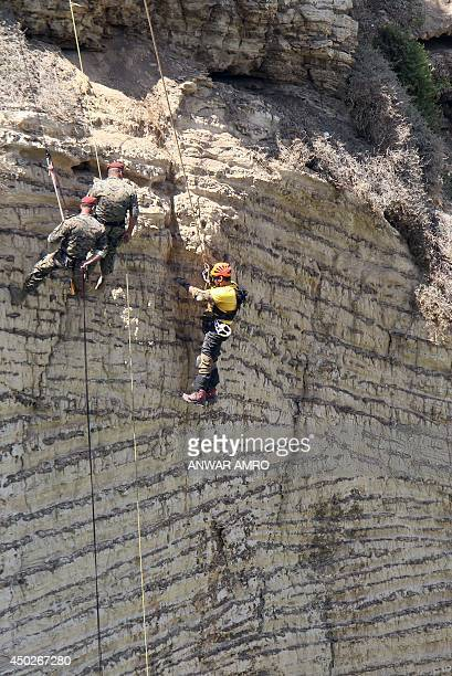 Lebanese army Navy seals look on as Michael Haddad a paraplegic ascends the 70 meter Pigeon's Rock a natural rock formation off the Rouche...
