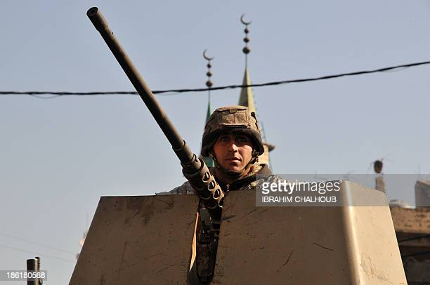 A Lebanese army soldier patrols a street with an armoured vehicle in the northern Lebanese city of Tripoli on October 29 2013 as army deployed...