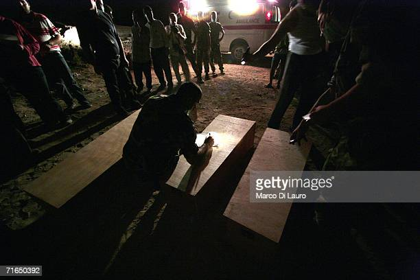 Lebanese Army soldier stands writes a name on a coffin containing a victim of the conflict with Hezbollah and Israel August 15 2006 in Tyre southern...