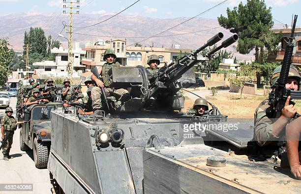 Lebanese army soldiers drive armoured personnel carriers in the northern Lebanese town of Arsal on the border with Syria on August 6 as fighting with...