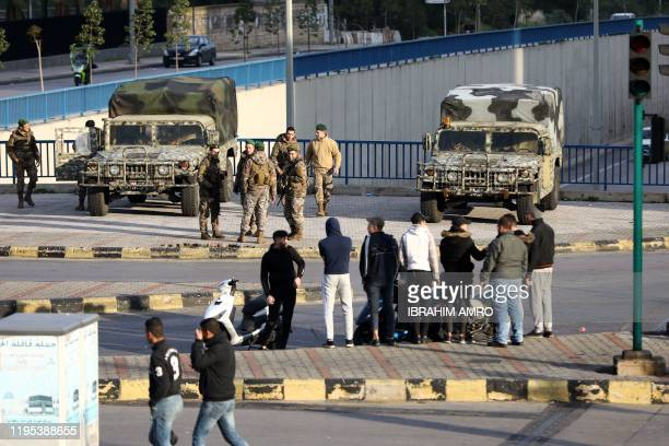 Lebanese Army soldiers gather next to a road blocked by antigovernment demonstrators next to the Camille Chamoun Sports City Stadium in the capital...