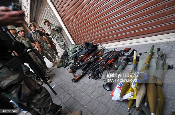 Lebanese army soldiers gather weapons and ammunition confiscated from an apartment following clashes with Islamist gunmen in the historic market of...
