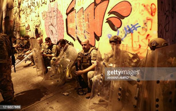 Lebanese army soldiers holding their shields rest in front of a wall covered with graffiti during a lull at a demonstration against dire economic...