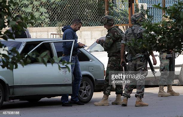 Lebanese army soldiers inspect a vehicle at a checkpoint on a road leading to Tripoli's Bab alTabbaneh Sunni neighbourhood on October 27 after troops...