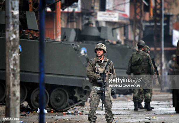 Lebanese army soldiers patrol a street in the northern Lebanese city of Tripoli on December 4 2013 as the army deployed following clashes between...