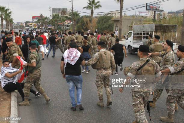 Lebanese army soldiers remove protestors blocking the main road between the southern city of Sidon and the capital Beirut on October 23 2019 as...